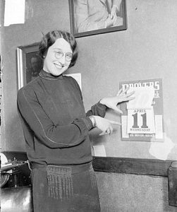 Three-quarter length portrait of Ellen Ryan holding up pages of a wall calendar and pointing at the calendar, standing in a room in Chicago, Illinois. Text on the calendar reads: April 11, Wednesday.
