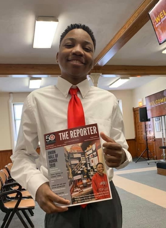 a portrait of Stephen Thomas holding a copy of The Reporter with his own photo on the cover