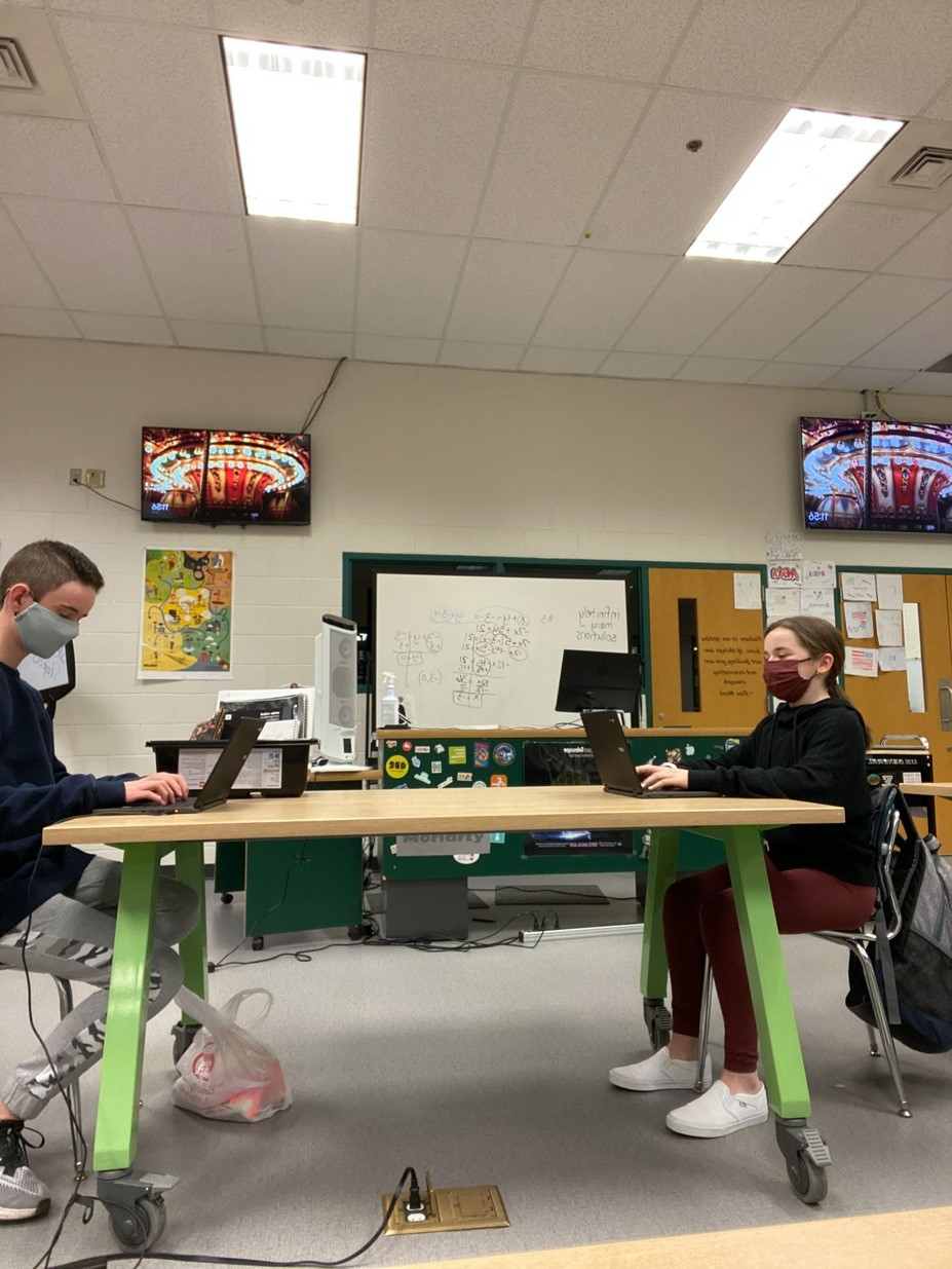 two students working at their laptops across a table from one another