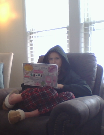 a photo of a student in an armchair working on a laptop