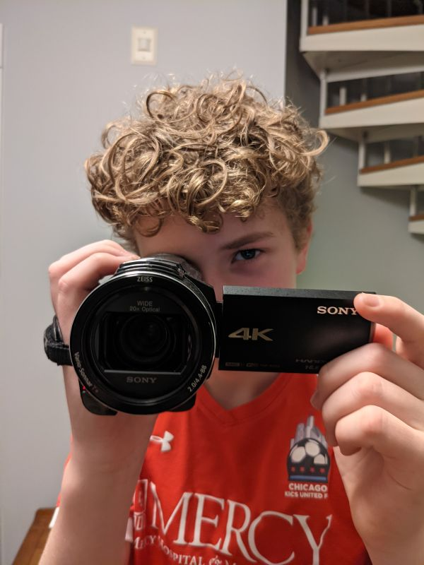 a student looking through the viewfinder of a video camera