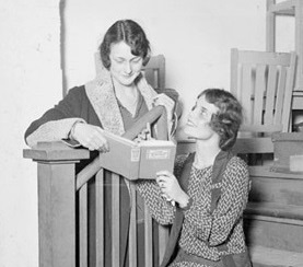 Half-length portrait of Daisiana Smith and Laverne Lowes holding a book in a room in Chicago, Illinois, at a Service Club charity benefit. One of the women is sitting on a flight of stairs, and the other is leaning over the banister.